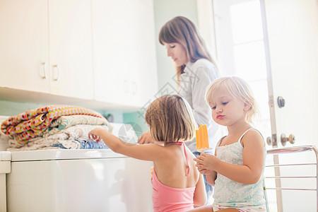 带折叠衣物的杂物室中的母亲和女儿图片