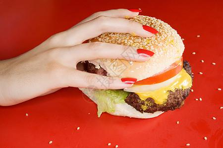 拿着汉堡的红指甲女人图片