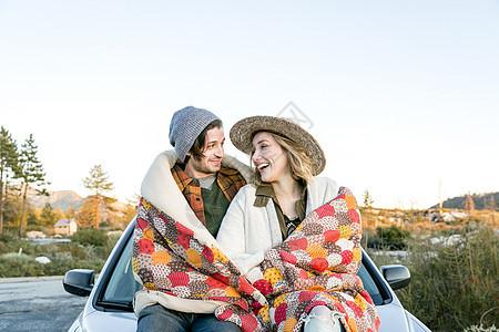 坐在汽车前的情侣图片