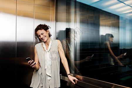 电梯里的女人看着手机图片
