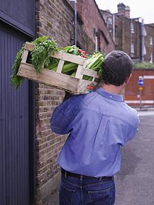 拿着一箱蔬菜的男人图片