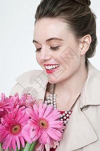 捧着盛开非洲菊的年轻女子图片