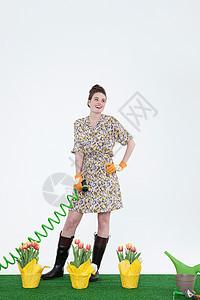 在人造草坪上带着软管和花的女人图片