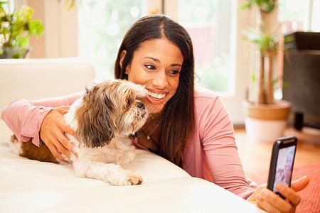 在智能手机上给自己和宠物狗拍照的女人图片