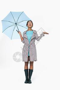 年轻女子撑着伞抬头看图片