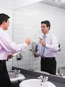 在办公室卫生间镜子里练习演讲的男人图片
