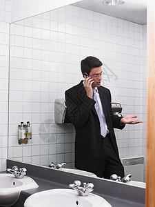 用手机反射在办公室卫生间镜子里的男人图片