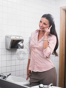 使用手机反射到办公室卫生间镜子中的女性图片