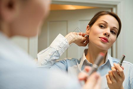年轻女子在浴室镜子里梳头图片