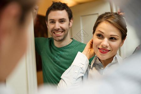 男人看着年轻的女人在浴室镜子里做头发,图片