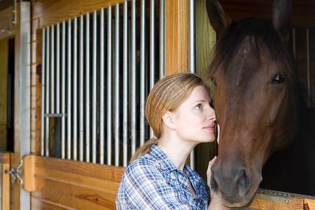 中年妇女和马厩里的马图片