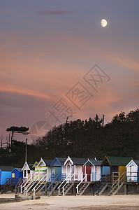 英国诺福克的月光下的一排彩色海边小屋图片