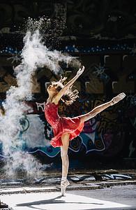 芭蕾舞女孩在涂鸦前撒白粉图片