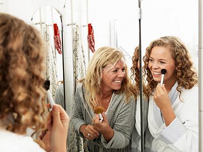 成熟女人在镜子里为女儿化妆图片