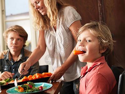 当妈妈端着胡萝卜吃健康餐的男孩图片