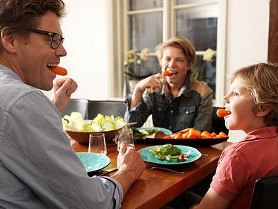 父亲和儿子坐在桌旁吃着健康的饭菜图片