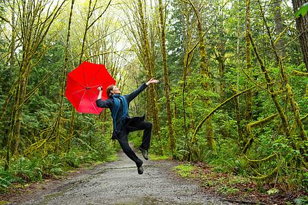 带着红伞在森林里跳跃的女人图片