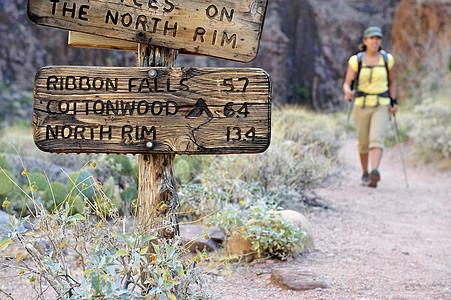 美国亚利桑那州弗拉格斯塔夫大峡谷女性徒步旅行者和乡村标志图片