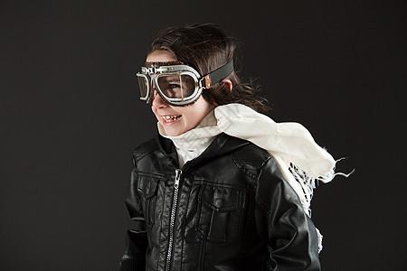 年轻的男孩戴着飞行护目镜打扮成飞行员图片