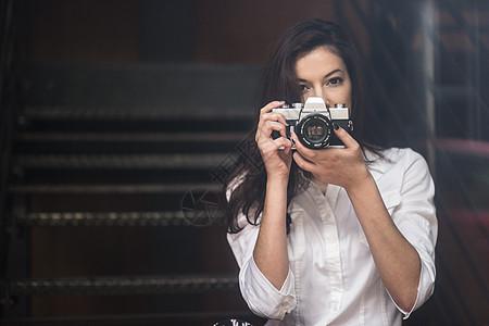 年轻女子用单反相机拍照图片