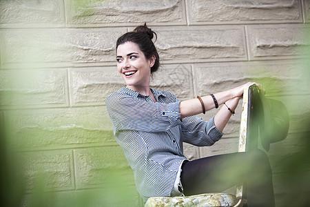 坐在外面椅子上的年轻女子图片