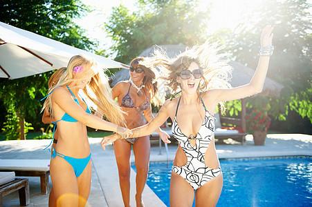 穿着泳衣在池边玩耍的女孩图片