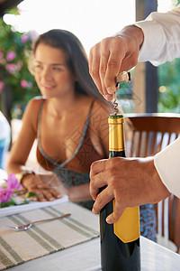 服务员在餐桌上打开酒瓶图片