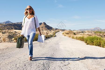 独自走在尘土飞扬的路上的女人图片