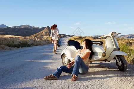 骑摩托车在路边休息的女人图片