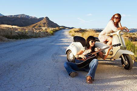 骑摩托车在路边休息的妇女图片