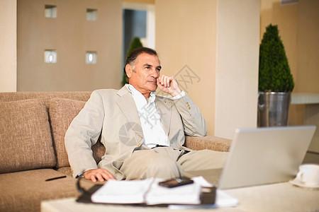 在沙发上工作的商人图片