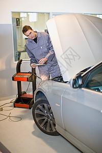 在检查汽车发动机的技工图片