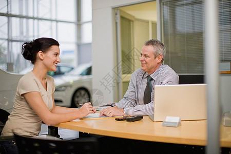 与汽车销售员交谈的女人图片