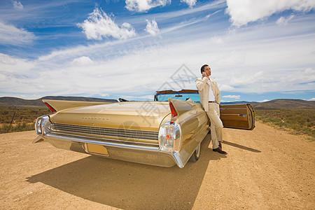 沙漠上一个男人靠在车边打电话图片