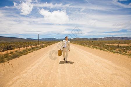 一个男人走在沙漠的路上图片