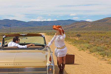 在沙漠路上搭车的女人图片