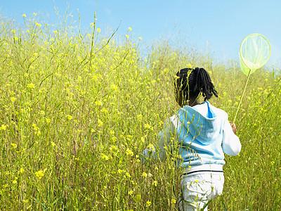 带着蝴蝶网的女孩在花丛里图片