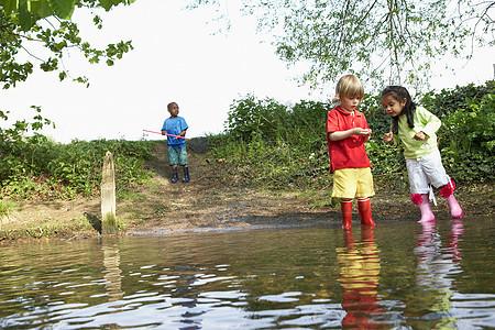 孩子们穿着雨靴在池塘边玩耍图片