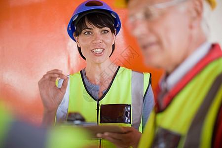 女建筑师与建筑工人交谈图片
