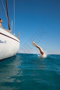 年轻女子从游艇上跳入大海图片