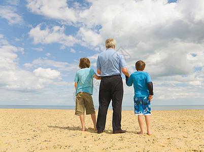 爷爷和两个男孩看着大海图片
