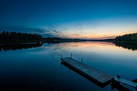 瑞典拉普兰斯凯尔夫特岛黎明时分的湖和木码头图片