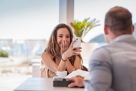 意大利撒丁岛卡斯蒂达斯海滩,一名年轻女子正在用智能手机给男朋友拍照图片