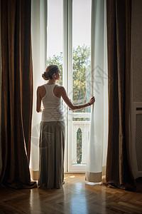 从客厅窗户向外看的优雅年轻女子图片