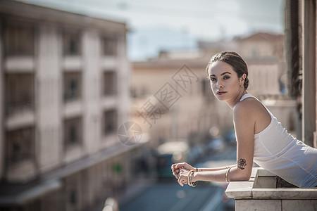 年轻女子在阳台上俯身图片