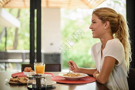 年轻女子在早餐桌上吃谷类食品图片
