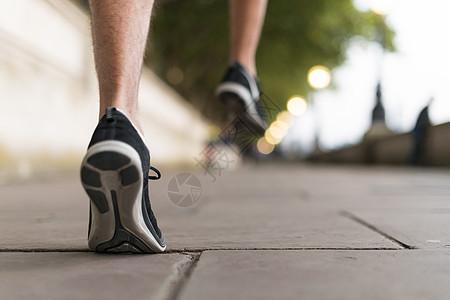 穿着运动鞋在人行道上跑步的年轻男性跑步者图片
