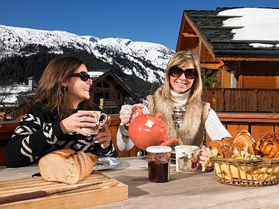 在露台上吃早餐的年轻妇女图片