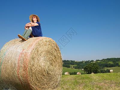 坐在一捆干草上的女孩图片