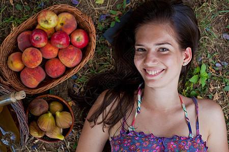 抱着一篮子水果躺在地上的女人图片